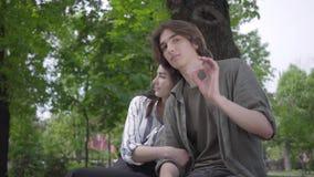 Пары портрета счастливые в случайных одеждах тратя время совместно в парке, имеющ дату Любовники сидя на стенде сток-видео