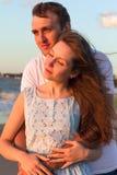 Пары портрета счастливые молодые ослабляя на пляже на заходе солнца Семья стоковая фотография rf