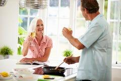 Пары постаретые серединой варя еду в кухне совместно Стоковые Изображения RF