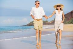 Пары постаретые серединой наслаждаясь прогулкой на пляже Стоковое Изображение
