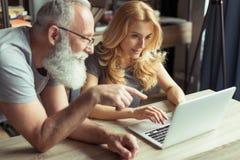 Пары постаретые серединой работая на компьтер-книжке совместно Стоковое Изображение