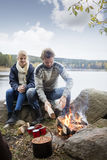Пары подготавливая костер во время располагаться лагерем берега озера Стоковые Фото
