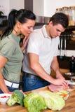 Пары подготавливая обед в кухне Стоковая Фотография