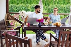 Пары предпринимателей нося приданные квадратную форму брюки пижамы имея завтрак стоковое фото rf