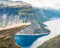 Пары представляя на Trolltunga Норвегии Стоковые Фотографии RF