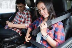 Пары прикрепляют ремень безопасности на раньше идти на автомобиле стоковое изображение