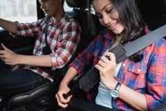Пары прикрепляют ремень безопасности на раньше идти на автомобиле стоковая фотография