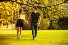 Пары принимая прогулку через парк Стоковая Фотография RF