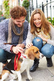 Пары принимая собаку для прогулки на улице города Стоковое Изображение RF
