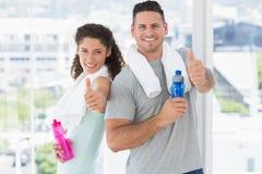 Пары при бутылки с водой показывать большие пальцы руки вверх на спортзале Стоковые Изображения RF