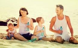 Пары при 2 дет выпивая свежую воду на песчаном пляже Стоковые Изображения RF