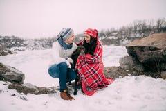 Пары при собака обернутая в красной шотландке во время зимы идут Стоковое Изображение