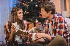 пары при чашки горячих пить и книга имея переговор в комнате стоковая фотография rf