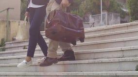 Пары при чемоданы идя вниз с лестниц outdoors, туристы на пути к гостинице видеоматериал