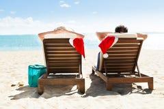 Пары при шляпы santa ослабляя на шезлонгах на пляжном комплексе Стоковое Фото
