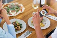 Пары при smartphone фотографируя еду на кафе стоковое изображение rf