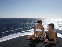 Пары провозглашать каннелюры Шампани на яхте Стоковая Фотография