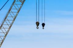 Пары промышленных подъемов крана на кабелях приближают к ферменной конструкции Стоковые Изображения RF
