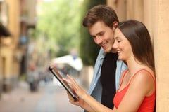 Пары просматривая таблетку в улице стоковое фото rf