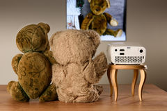 Пары плюшевого медвежонка наблюдая их фото с мини репроектором Стоковые Изображения RF