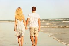 Пары пляжа держа руки идя на заход солнца Стоковая Фотография