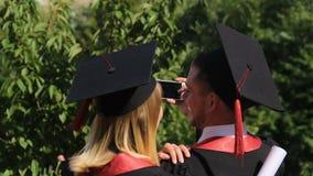 Пары радостных студент-выпускников записывая видео на smartphone, выпускную церемонию видеоматериал