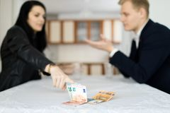 Пары разрешая финансовый кризис совместно на таблице в кухне стоковые фото