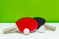 Пары ракеток пингпонга и белых шариков, на светлом gre Стоковые Изображения