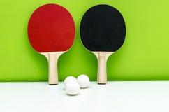 Пары ракеток пингпонга и белых шариков, на светлом gre стоковое фото