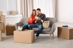 Пары распаковывая картонную коробку пока отдыхающ на софе в их новом доме стоковые фотографии rf