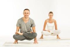 пары располагают сидя йогу Стоковое Изображение RF