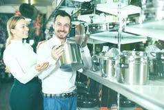 Пары рассматривая различные кастрюльки в магазине dinnerware Стоковые Изображения