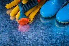 Пары резиновых ботинок кроют кожей перчатки безопасности и шланг сада Стоковое Фото