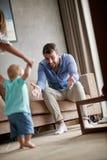 Пары родителей помогая их младенцу сделать первые шаги в thei стоковые фото