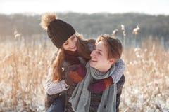 Пары рождества счастливые в объятии влюбленности в лесе снежной зимы холодном, космосе экземпляра, торжестве партии Нового Года,  стоковая фотография rf