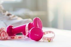 Пары розовых гантелей фитнеса с лентой сантиметра на яркой Стоковая Фотография RF