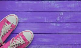 Пары розовых тапок на фиолетовой несенной деревянной предпосылке Стоковое фото RF