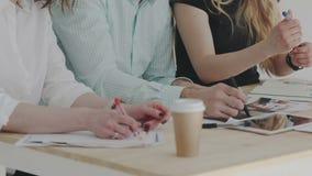 3 пары рук на таблице Поток операций конца-вверх в офисе дневного света Дизайнеры связывают и планируя новое понятие сток-видео