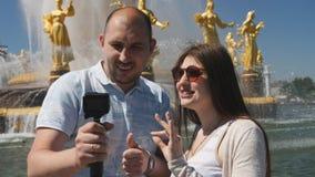 Пары сами блоггеров снимают и видимости во время отключения Соедините блоггеров от величественного фонтана в a сток-видео