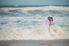 Пары свадьбы стоя влажный в морской воде стоковые фотографии rf