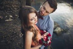 Пары свадьбы целуя и обнимая на утесах приближают к голубому морю стоковые изображения rf