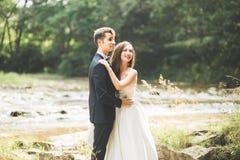 Пары свадьбы, groom и невеста обнимая, внешнее близко река стоковая фотография rf