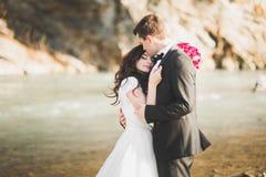 Пары свадьбы, groom и невеста обнимая, внешнее близко река стоковое изображение