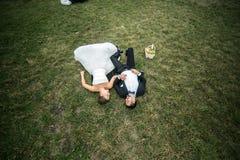 Пары свадьбы лежа на траве стоковая фотография rf