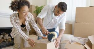 Пары связывая коробки тесьмой по мере того как они пакуют вверх по их дому Стоковое Изображение