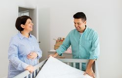 Пары семьи аранжируя кровать младенца с тюфяком стоковое изображение