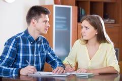 Пары семьи на столе с финансовыми документами внутри помещения стоковое фото rf