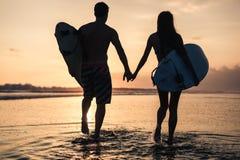 Пары серферов над заходом солнца на береговой линии Стоковое Фото