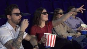 2 пары сидят в кино и едят попкорн стоковые фото