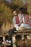 Пары сидя на доках озера стоковые изображения